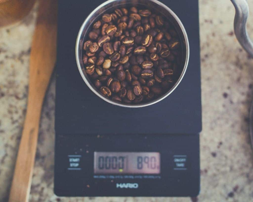 Digital scales weighing a pot of coffee beans