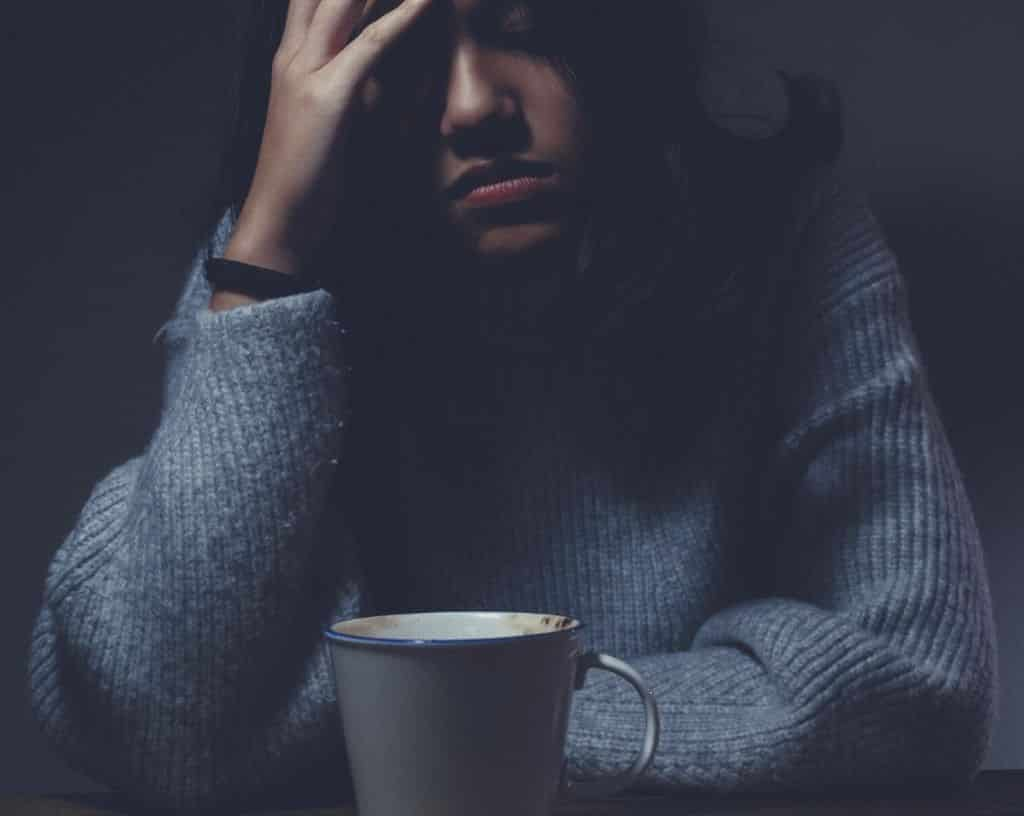 A sick woman drinking coffee