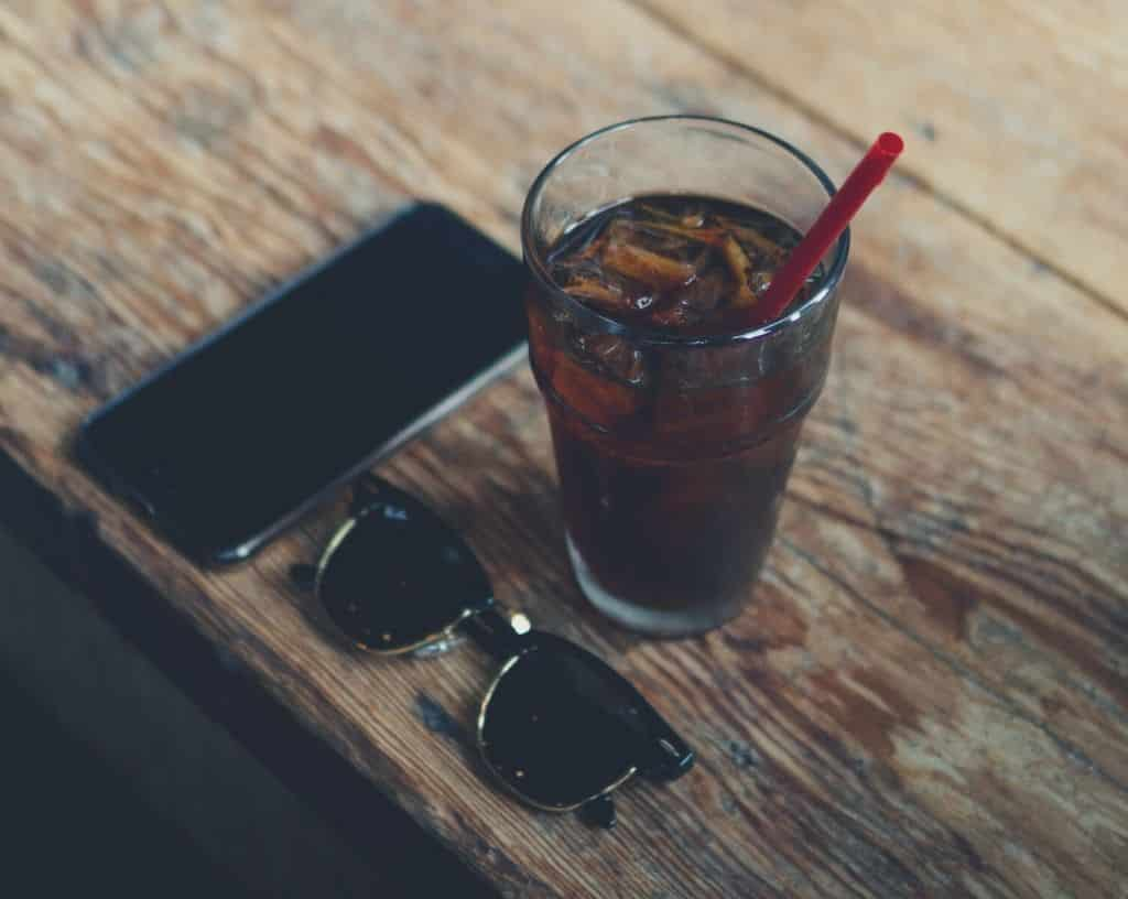 A glass off cold brew coffee, sat next to a pair of sunglasses and a smart phone