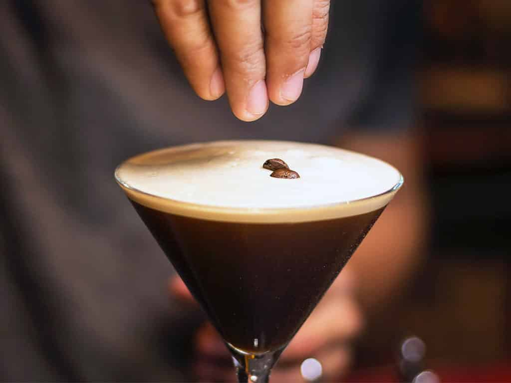 An espresso martini with coffee beans being added to the top